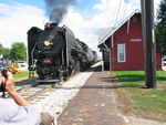 Steam train leaves Geneseo; the train is going away from us.