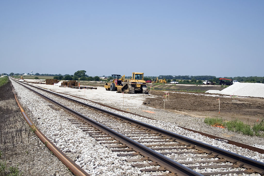 Looking west from 2900E crossing.  New rail ready for mainline and land graded for new yard north of mainline and siding.   August 10, 2007.