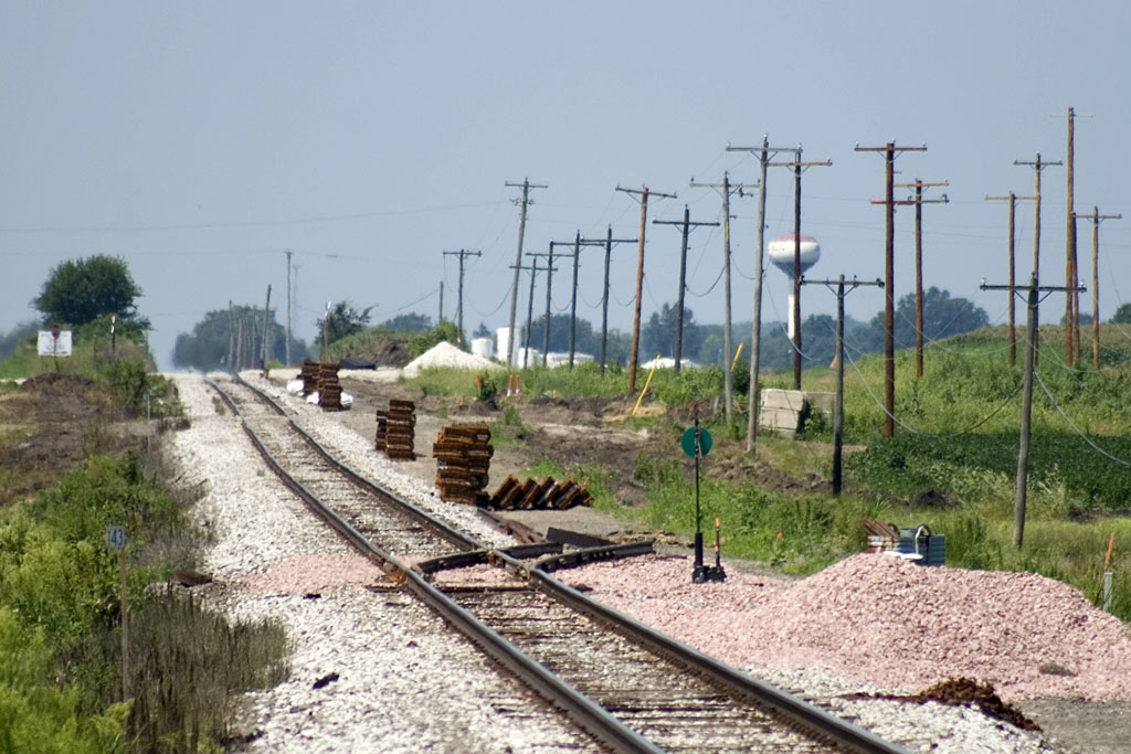 Looking west at the east siding switch, located at the Henry/Bureau County line.  Steel ties stacked and waiting for placement for new siding.   August 10, 2007.