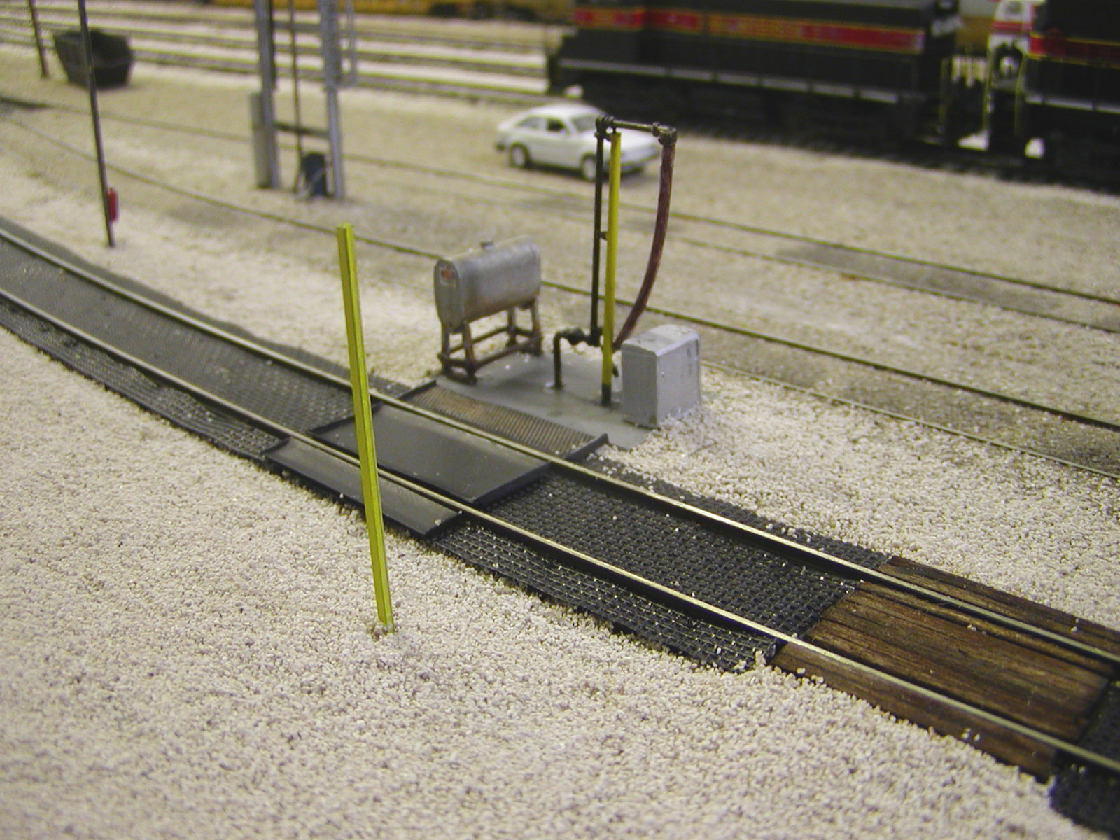 "New fuel pad, fuel spill containment trays and mats, support/guard posts made from old rail, grade crossings for MOW hostlers and their equipment, and buried enginehouse tracks.  The fuel pipe was heavily kitbashed from a pair of American Limited Models fuel cranes, while the fuel spill collection trays are scratchbuilt from 0.010"" styrene and Scale Scenics mesh.  The fuel spill mats are garden weed cloth.