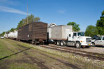 The Asplundh weed spray train on the left and Asplundh's supply truck on the right.  The trailer is one of the original roadrailer trailers, still tricked out with center railroad wheel between the 2 road axles!
