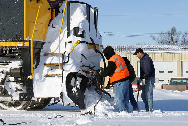 Workers use a torch, bar and maul to clean the packed snow from front coupler.