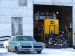 IAIS 151 peaking out from with the Iowa City engine house, along with a vintage 1960's Pontiac.