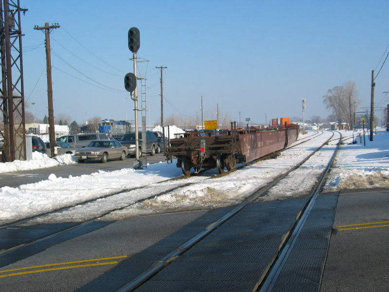 The east train clears the main at Vermont St., while the CRL is coming out of Roll Lumber in the background.