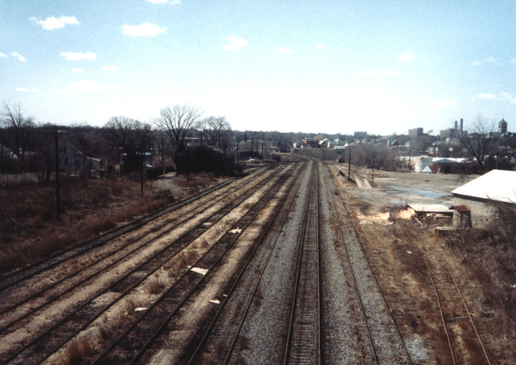 The IAIS yard in Iowa City looking west  from the Dodge Street Bridge. Notice to the left center of the picture is the old Rock Island engine house hidden in the shadows.