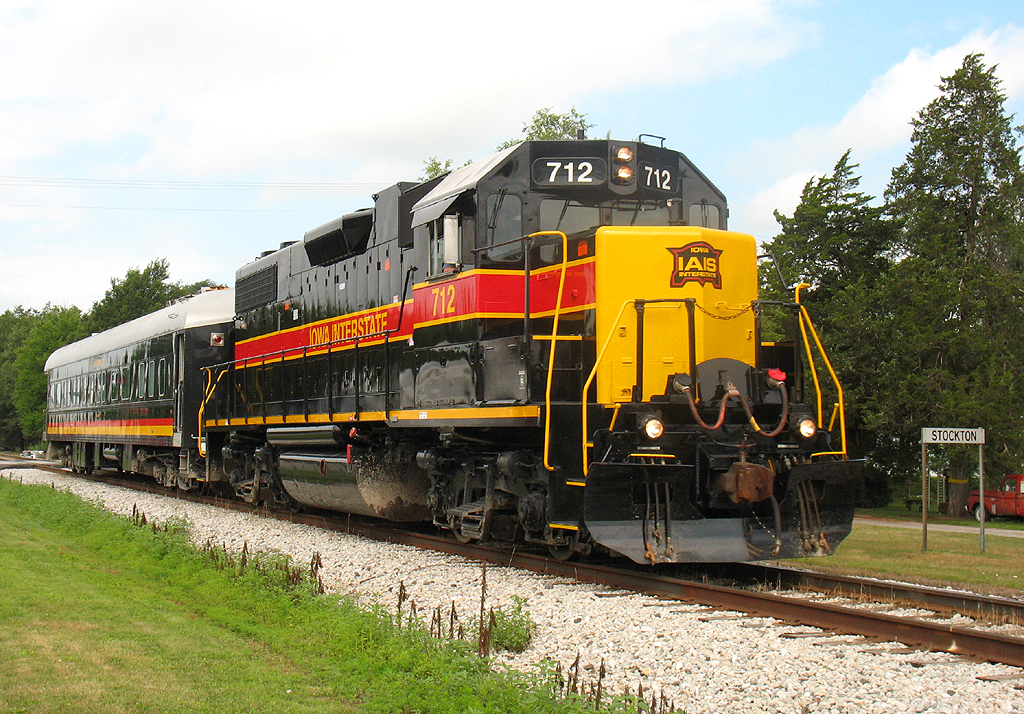 "IAIS 712 pulls business car ""Hawkeye"" east through Stockton, IA on 26-Jul-2006."