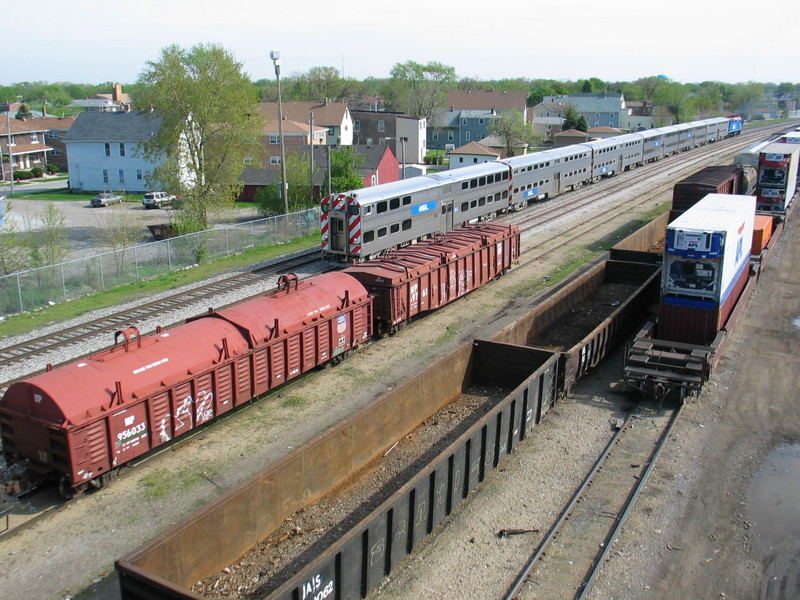 Inbound mainline express passes the IAIS's yard tracks at RI's old Burr Oak yard, below 127th St.  The 2 UP system covered gons were right behind the power on the departing westbound.
