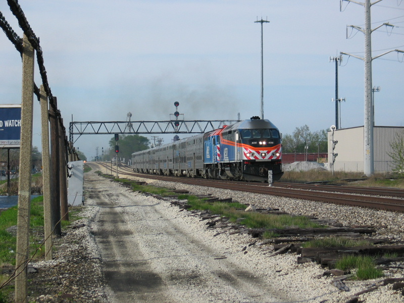 May 2, 2007. Looking north along the main line at Gresham as an outbound suburban train approaches.  Notice at right, the back of the 3 head signal controlling movements off the South Chicago line.