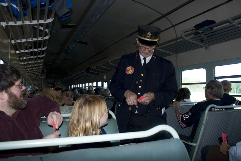 Volunteer Conductor Jerry Stauffer punches tickets.  1500 trip to Walcott behind IAIS 7081.