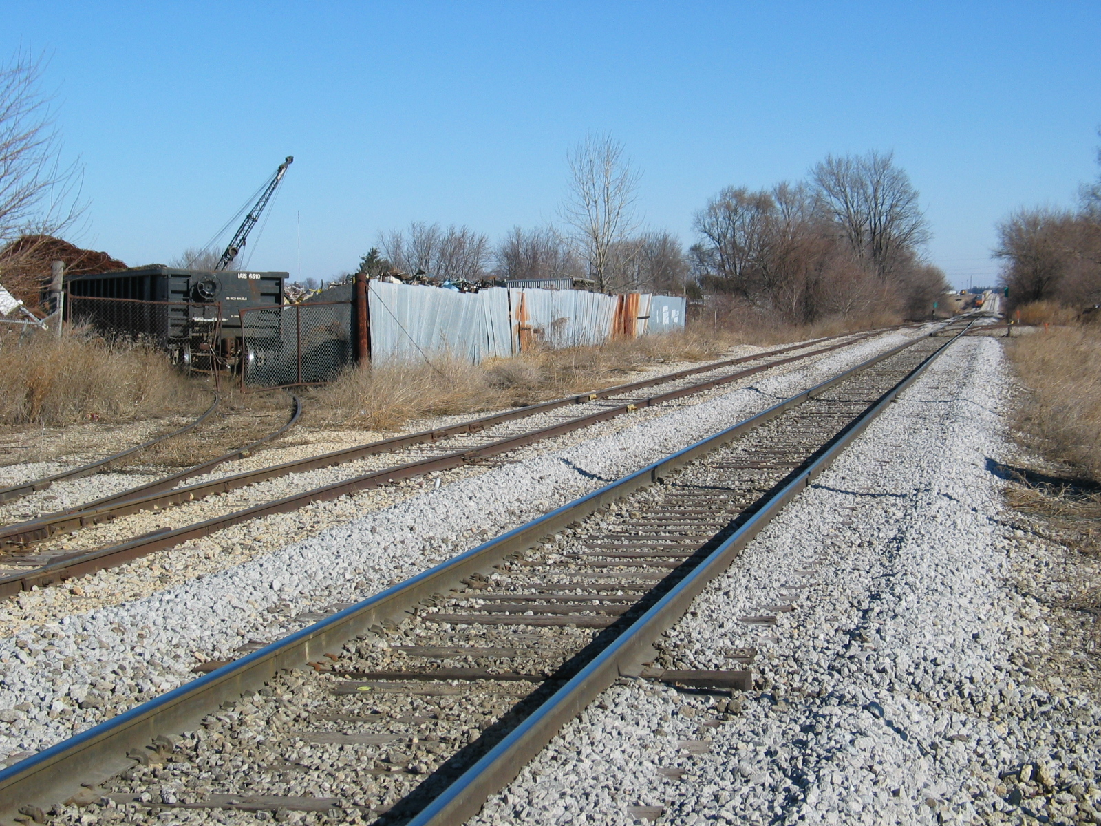 Scrap hopper (IAIS 6500 series) at Gralnek, in Newton.  In the background is the tail end of the eastbound on the siding.  Jan. 13, 2006.