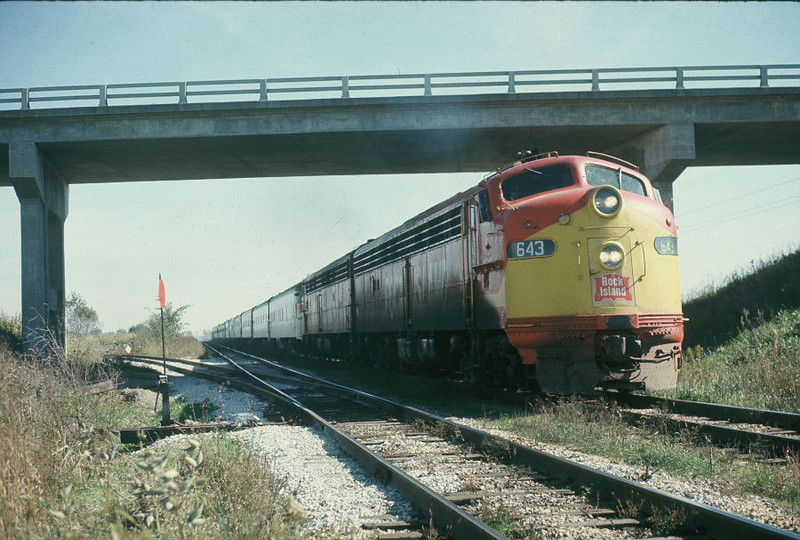 Westbound football special at the Wilton overpass, Oct. 20, 1973.  This scene is essentially the same today, with the exception of the aluminum guard rail on the overpass being replaced by a concrete one during a widening project 10 years ago or so, welded rail is now in place on the track the train is on, and the former westbound main in the immediate foreground is now part of N. Star siding.