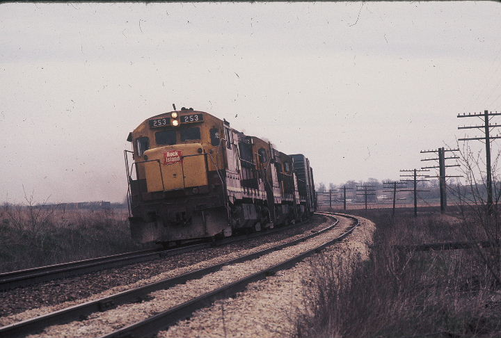 Westbound freight rounds my favorite curve east of Atalissa, April 26, 1975.