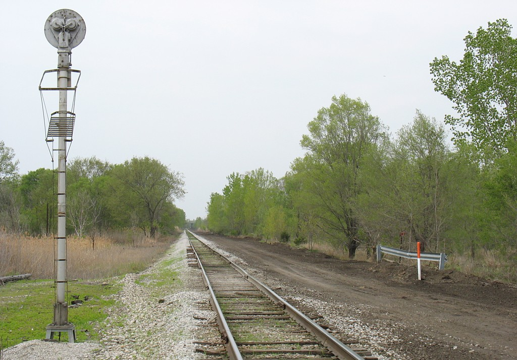 Looking west from the grade crossing in Carbon Cliff, IL.  The graded area on the north side of the mainline will be the new siding.  April 28, 2006.