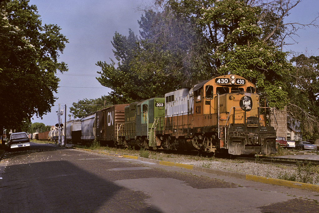 "IAIS 430 pals up with the ""Green Bean"" on a westbound manifest at Davenport, Iowa June 10th, 1992."