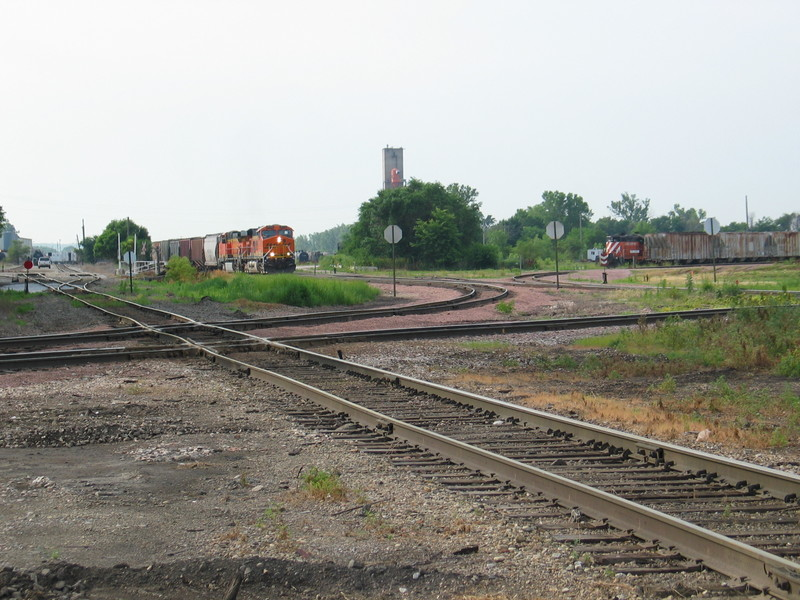 BN train is backing up the Bayard line, in the foreground is IAIS's main, crossing it is BN's Pacific Jct. line, and in the background is CBGR's geep.  Council Bluffs, June 21, 2006.