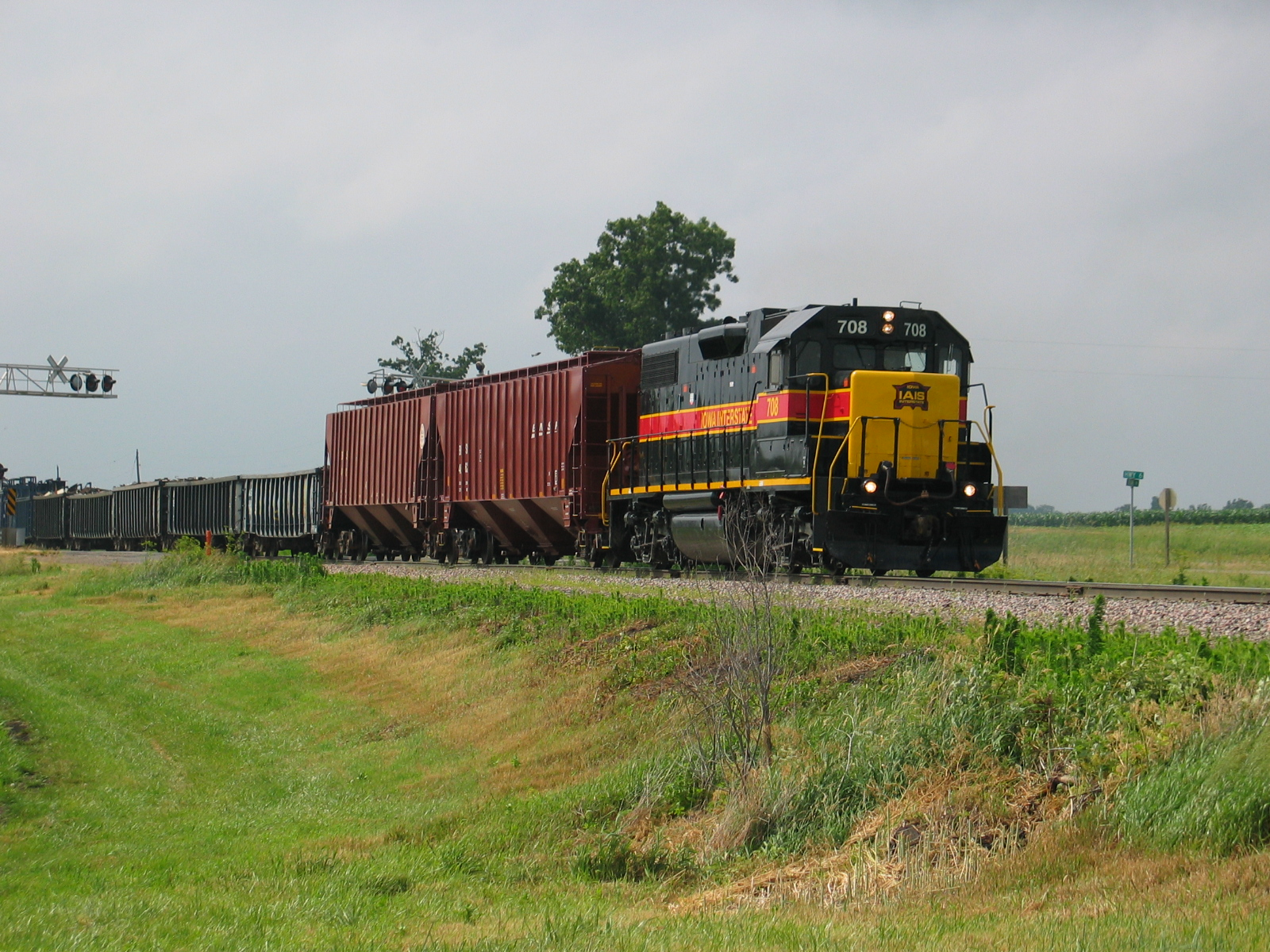 Eastbound Wilton Local at the highway 6 crossing west of West Lib., with 2 fertilizer loads for Atalissa on the head end, June 18, 2007.