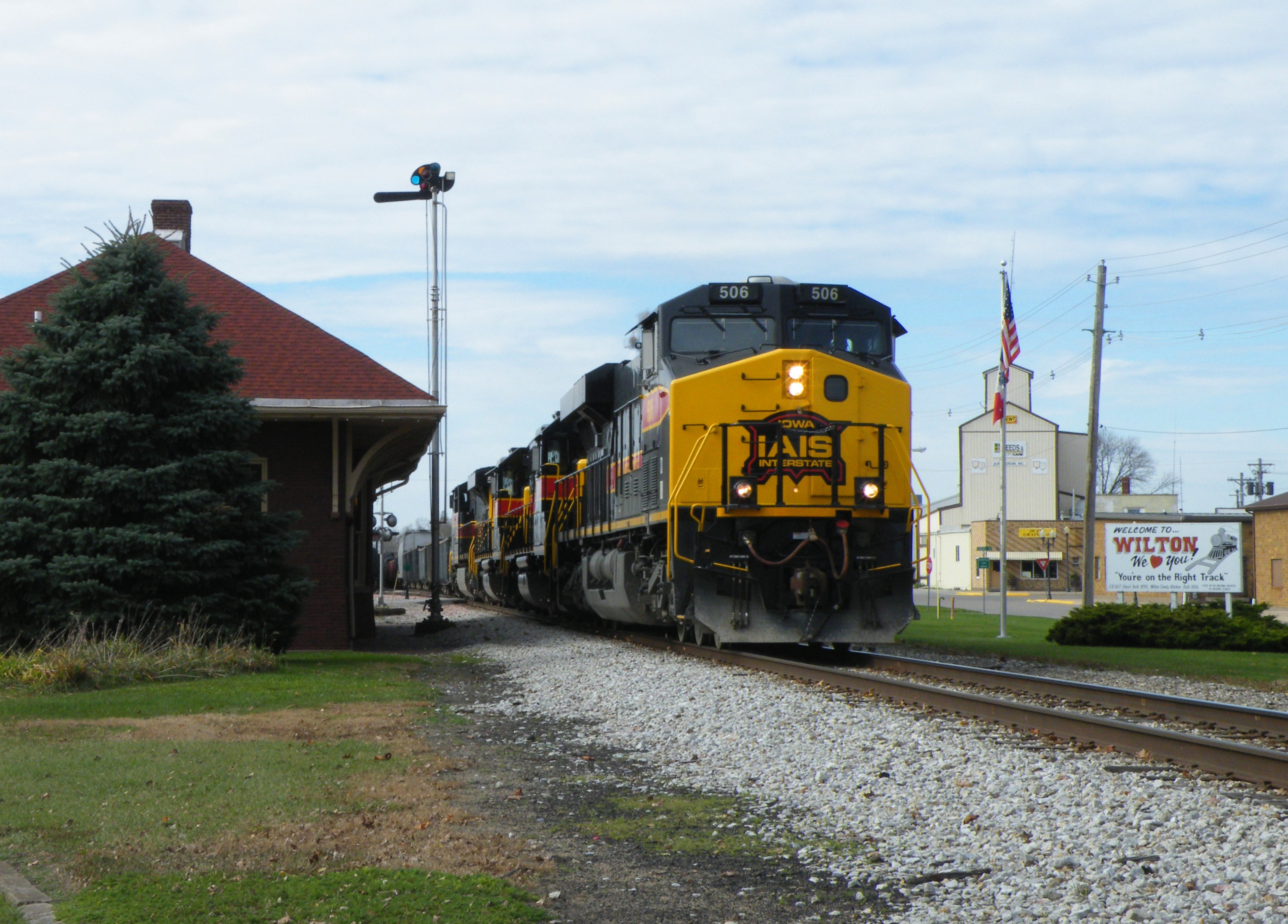Rollin' right along, 506 makes great time by the depot in Wilton, IA.