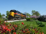 Spring is in full bloom, pun intended, as Iowa's BUSW rolls toward Mossville with the empty CRPE coal train.