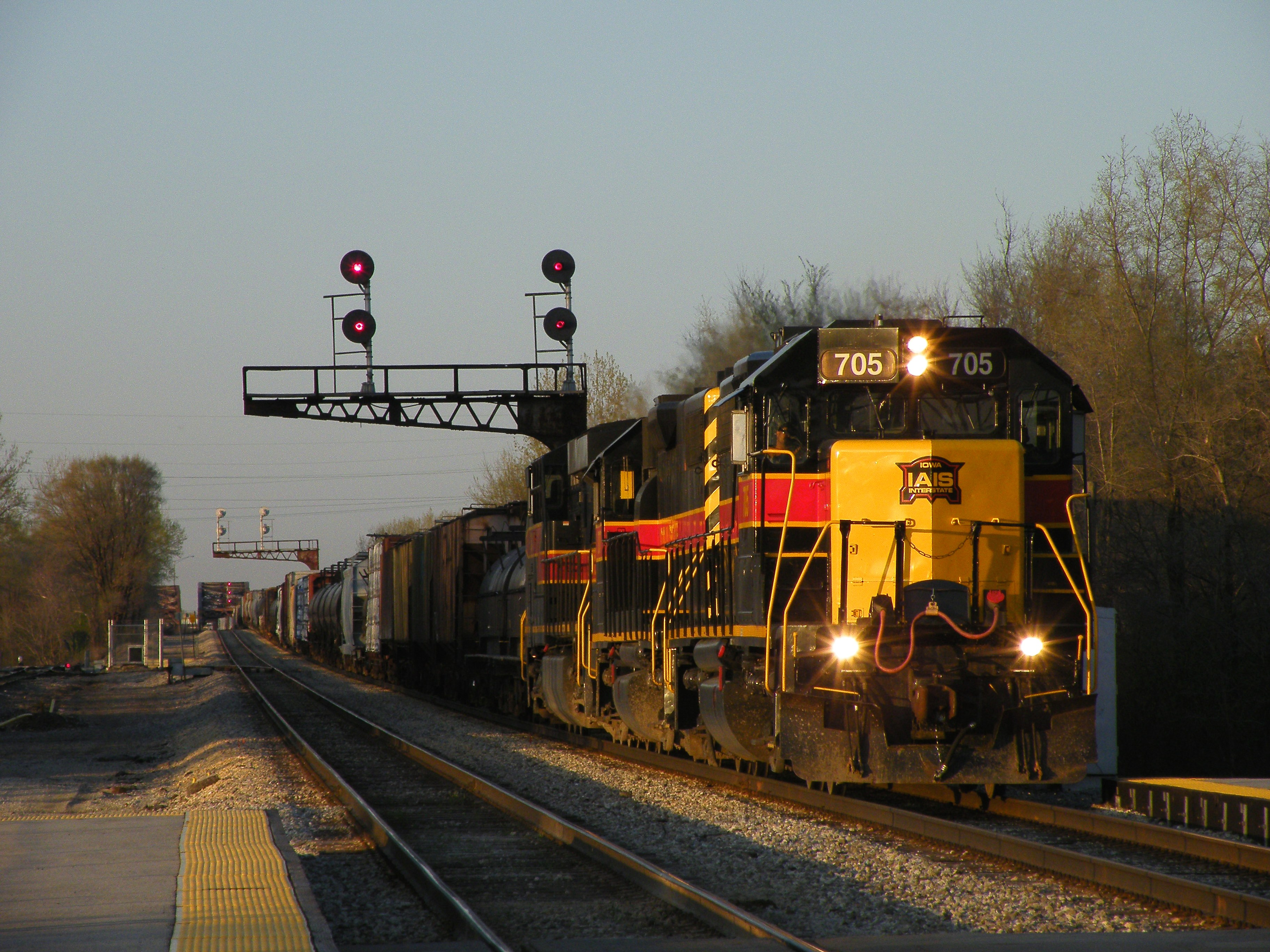 Iowa 705, 707, and 509 lead the daily westbound BICB roadfrieght into the setting sun behind Metra express 421. Each day is getting longer and longer, shots like this more and more common. 04-09-10