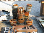 Here are a couple EMD 645 power assemblies.  The rusty silver cans sitting on top are pistons; two cylinder heads are laying on the ground on each side, with 4 exhaust valves per head.  Visible on the cylinder liners is the row of air inlet ports; when the piston reaches the lower end of its stroke these ports are uncovered while simultaneouly the exhaust valves open.  Pressurized air from the blower/turbocharger then rushes into the cylinder through these ports, giving a fresh charge of air while also pushing the exhaust gases out through the valves.  As the piston comes back up it covers the ports again, the exhaust valves shut, and the air is then compressed by the piston.  At or near top dead center the injector (not visible, but it goes in the middle of the head) will inject a measured amount of fuel, and the heat from compression will ignite the fuel, beginning the power stroke.