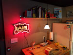 I decided to design and fabricate a neon IAIS logo for the layout room. I drew the logo up and had the black base CNC'd out of plexi, added reflective yellow type, and had a local custom neon artist create the red accent line out of neon. I also decided to place the sign above one of my work spaces rather than on the layout valance.