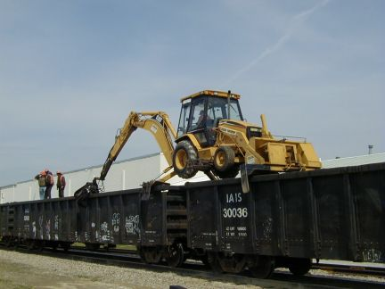 Moving the backhoe to the next car.