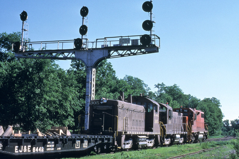 An eastbound EJ&E local passes under the iconic R.I. signal cantilever(s) at Bureau, IL. Photo by John Dziobko