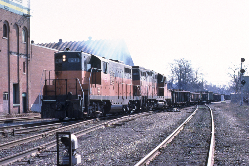 Milwaukee Road service on the former Rock between Davenport and Iowa  City as a short train for North Star Steel in Wilton has finished it's reverse move out of West Dav yard and begins the assault up the hill in Davenport. March 1981. Photo by John Dziobko