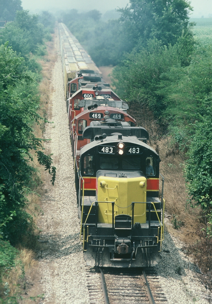 483, 469, 600, and another Geep handle a grain train east of Iowa City. August-1989.
